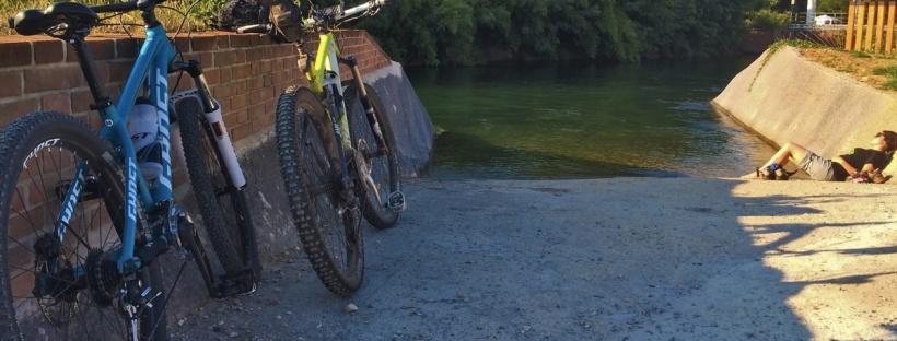 in foto due biciclette e una persona sdraiata a prendere il sole in riva al canale villoresi