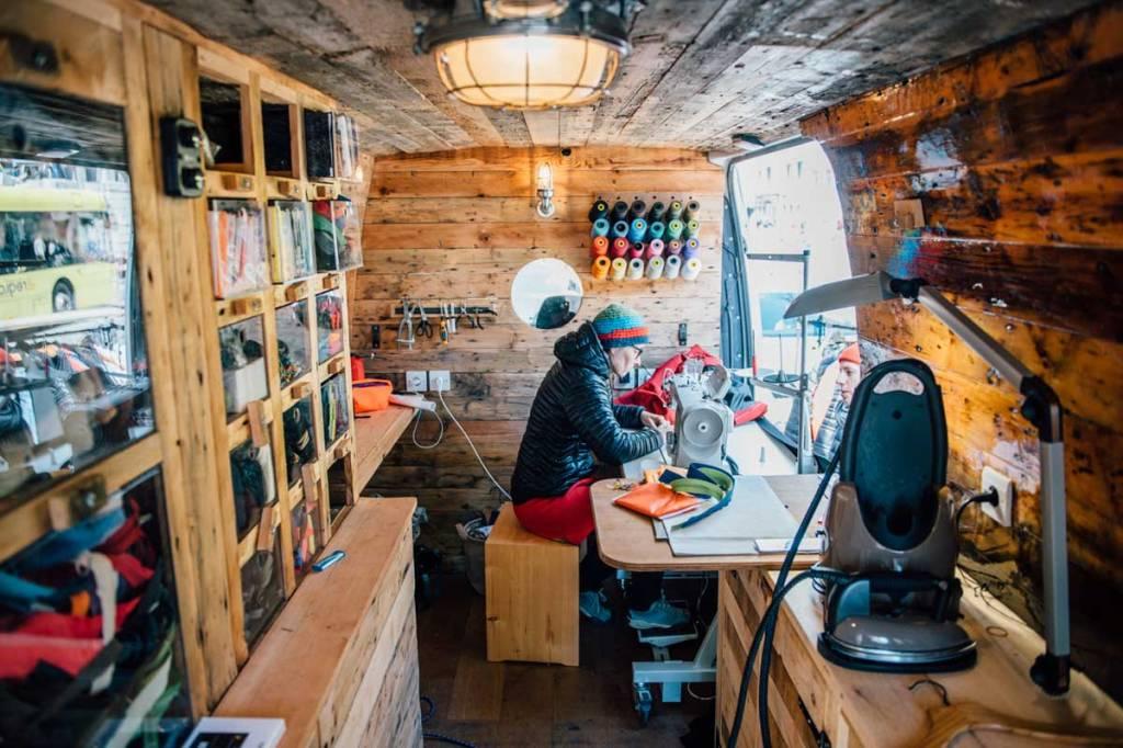 una persona all'interno di una casetta di legno allestita per riparare capi di abbigliamento