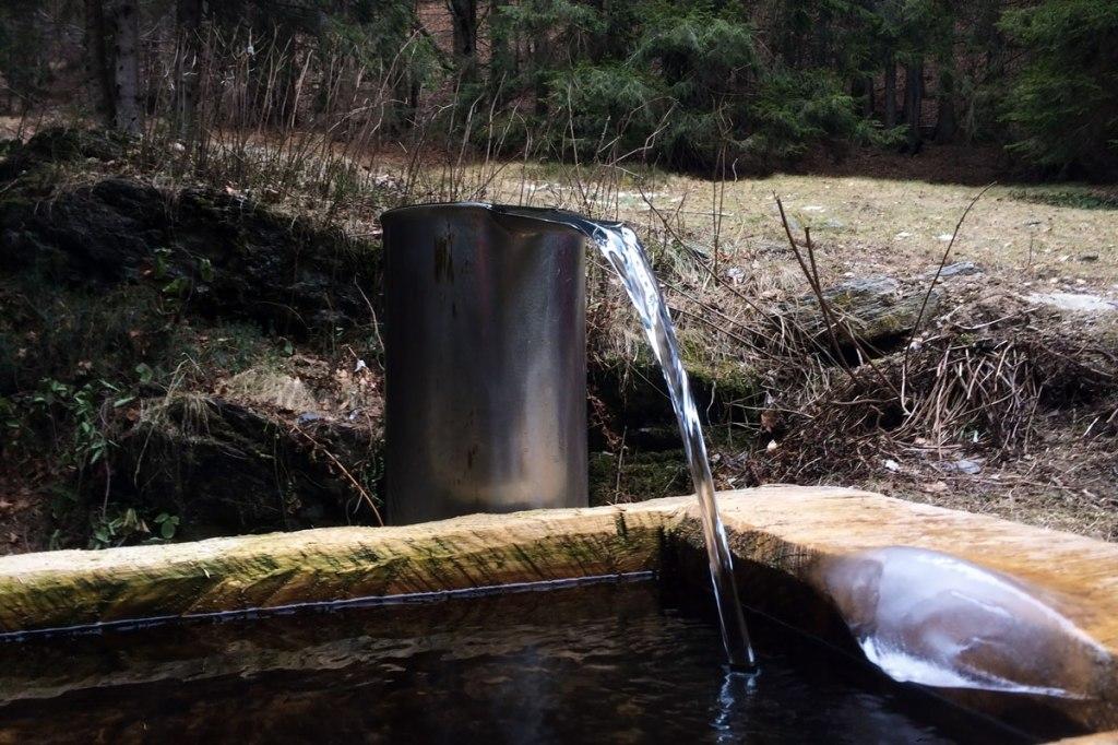 l'acqua che fuoriesce da un ugello in acciaio lucido si riversa in una vasca di legno perfettamente intagliata