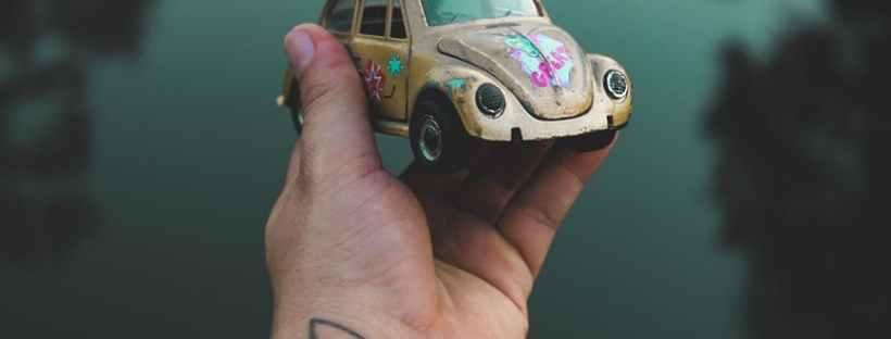 modellino di maggiolino volkswagen classico giallo con graffiti è sorretto da un braccio tatuato
