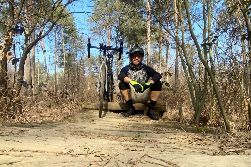 ciclista seduto con bicicletta di fianco nei boschi del parco delle groane