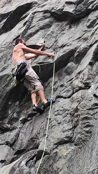 alpinista arrampica su parete di roccia