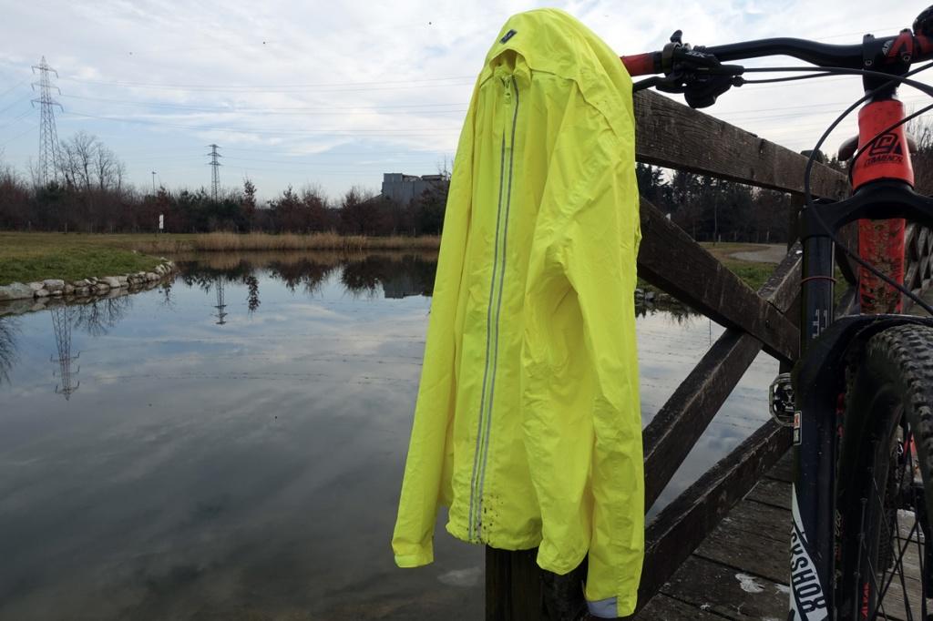 in foto una giacca antipioggia gialla fluorescente con sullo sfondo un laghetto artificiale