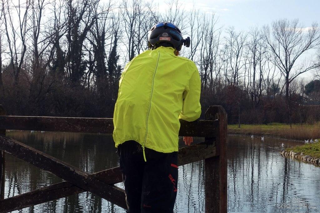 in foto un ciclista indossa una giacca antipioggia nei pressi di un laghetto artificiale