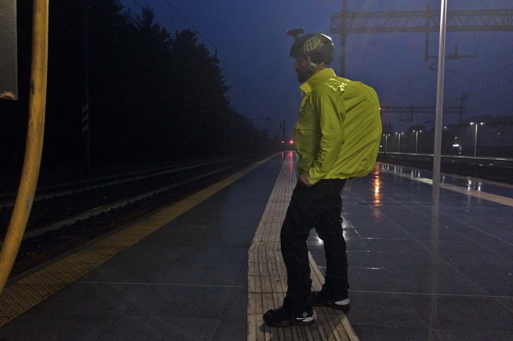 in foto un ciclista sotto il temporale indossa una giacca e un pantalone antipioggia