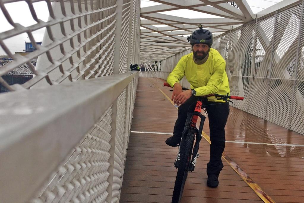 in foto ciclista sotto il temporale indossa giacca e pantalone antipioggia