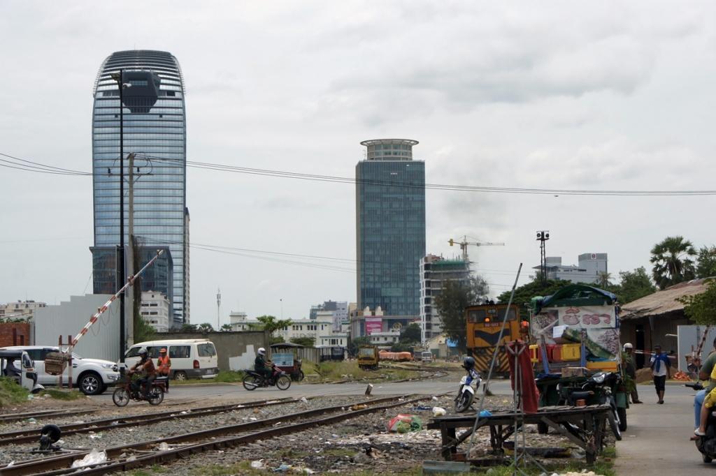 nella foto baracche a phnom phen, lavoratori che si spostano in moto, il grattacelo coreano ed il grattacielo cinese vicino i binari del treno