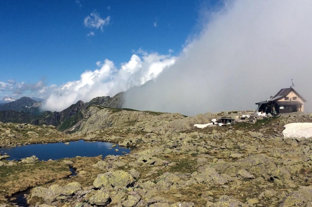 in foto il rifugio cesare benigni avvolto parzialmente dalle nuvole mentre un'altra parte del cielo è limpidissima
