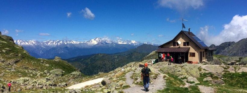in foto il rifugio benigni adagiato su un altopiano alla base della cima piazzotti e poco distante dall'omonimo lago