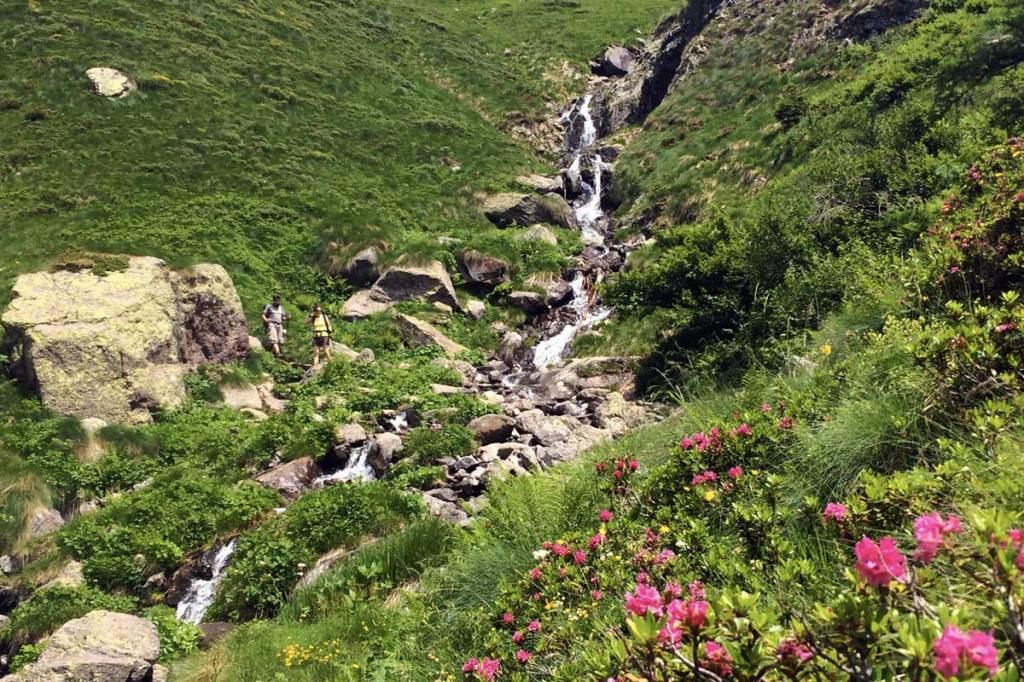 in foto due escursionisti in discesa approcciano un ruscello che attraversa un sentiero nelle orobie bergamasche
