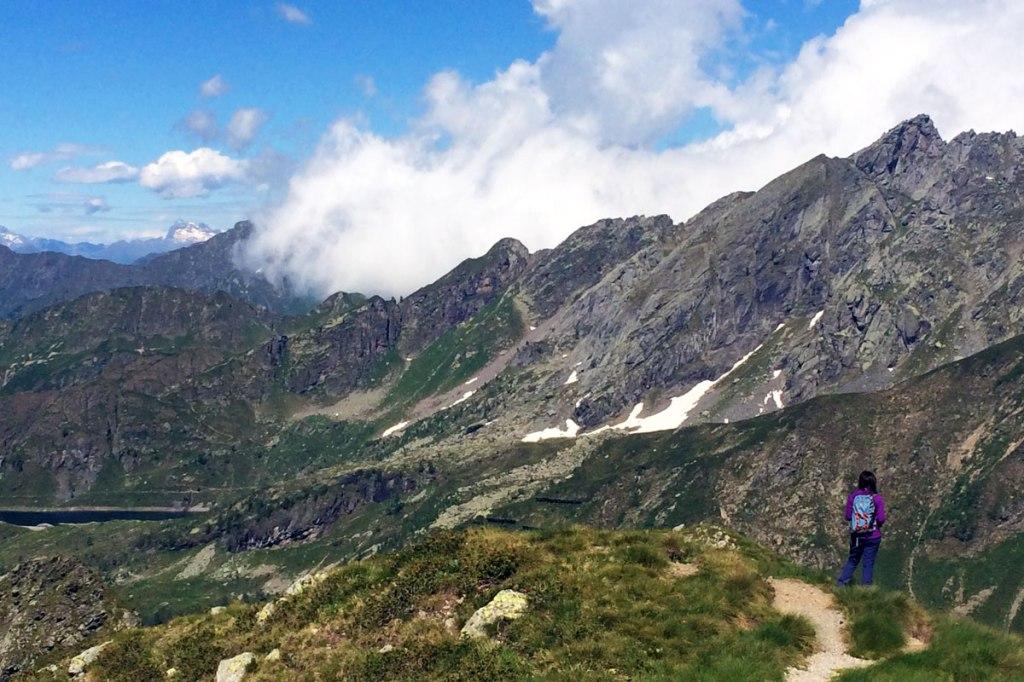in foto una ragazza si gode la vista sulla vallata dall'altopiano su cui è collocato il rifugio benigni ai piedi della cima piazzotti