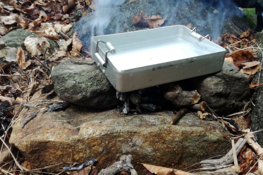 un gavettino in alluminio sul fuoco per scaldare l'acqua e preparare un caffè