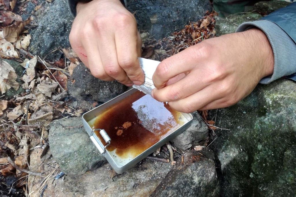 in foto un escursionista versa caffè solubile nell'acqua per preparare una bevanda calda