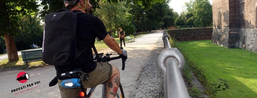 un ciclista in sella alla sua gravel bike è fermo al castello sforzesco di milano