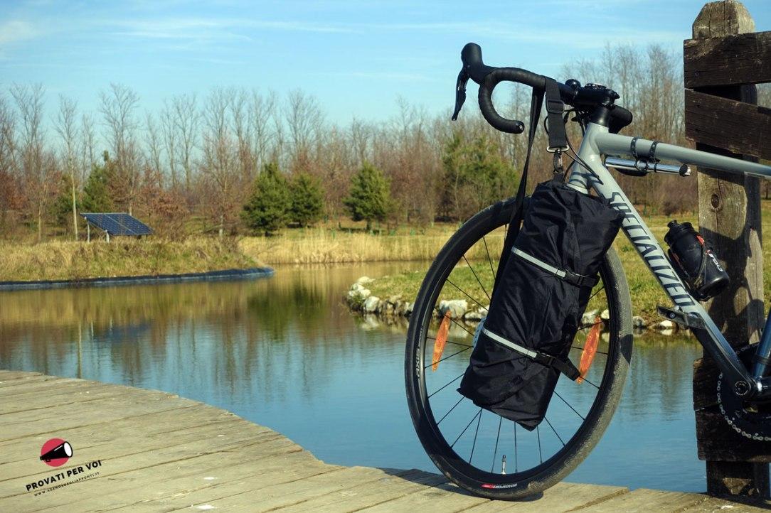 una bicicletta fotografata con una custodia porta abiti impermeabile appesa al manubrio