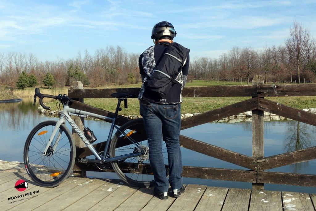 un ciclista fotografato vicino alla sua bicicletta con una custodia porta abiti a tracolla