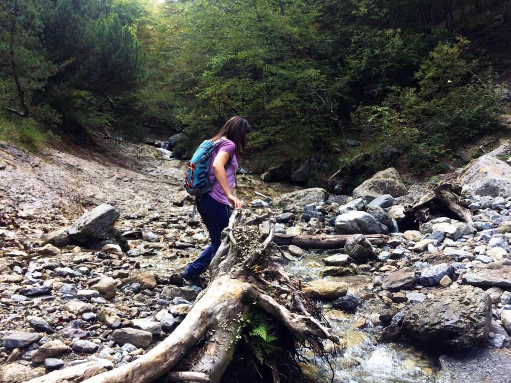 escursionista a piedi si accinge ad affrontare il guado di un torrente di montagna sulla Grigna Meridionale