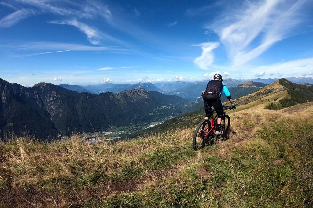un ciclista scende con la mountain bike lungo una cresta erbosa con panorama sulle montagne lombarde e le valli