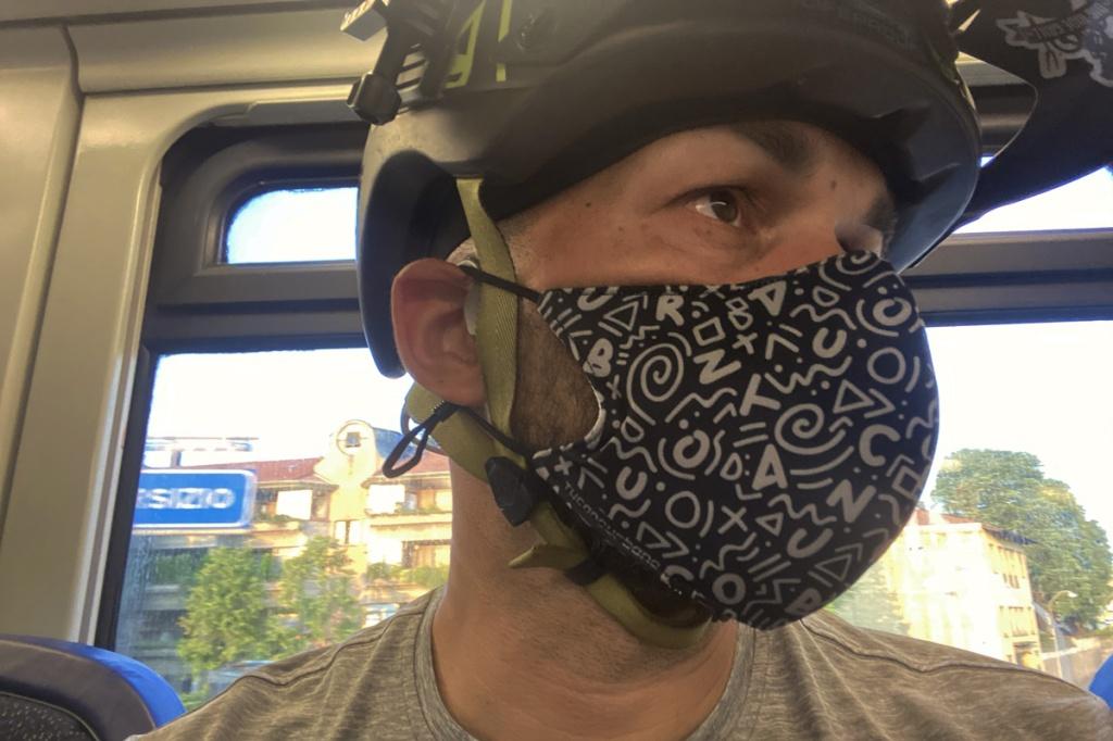 un ragazzo in treno indossa una mascherina filtrante di cotone con sopra il casco da bicicletta