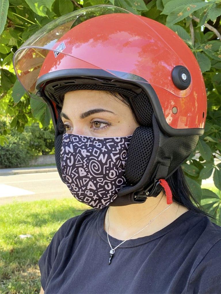 una ragazza indossa una mascherina filtrante in cotone con il casco da moto