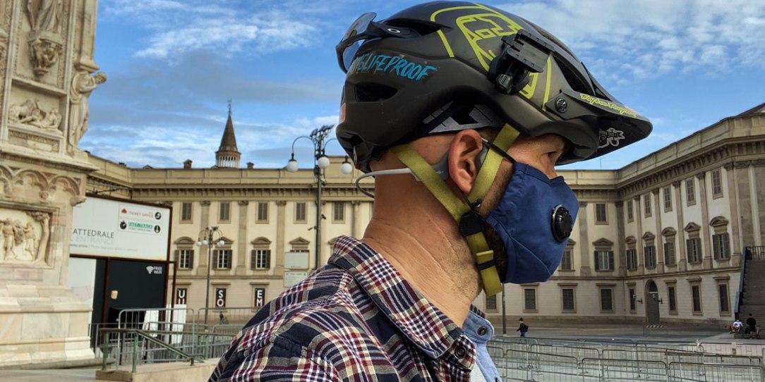 un rider milanese con casco, mascherina e cuffie a conduzione ossea nella piazza del Duomo