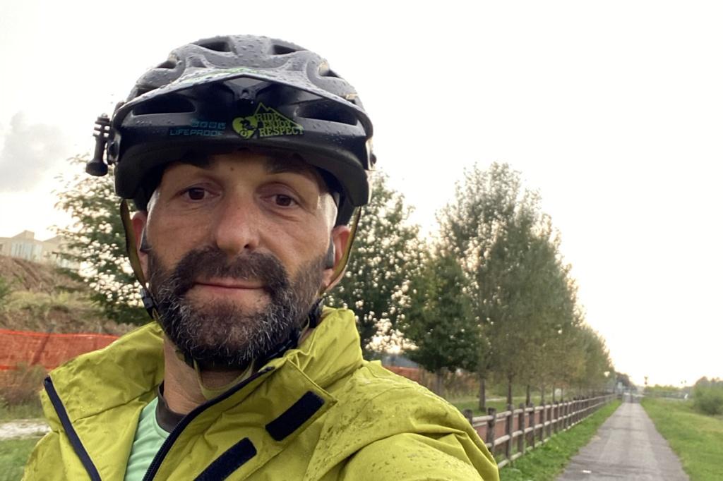 un ragazzo in bicicletta sorridente sotto la pioggia