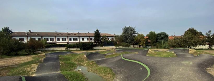 una pista pump track per biciclette e monopattini con delle case sullo sfondo