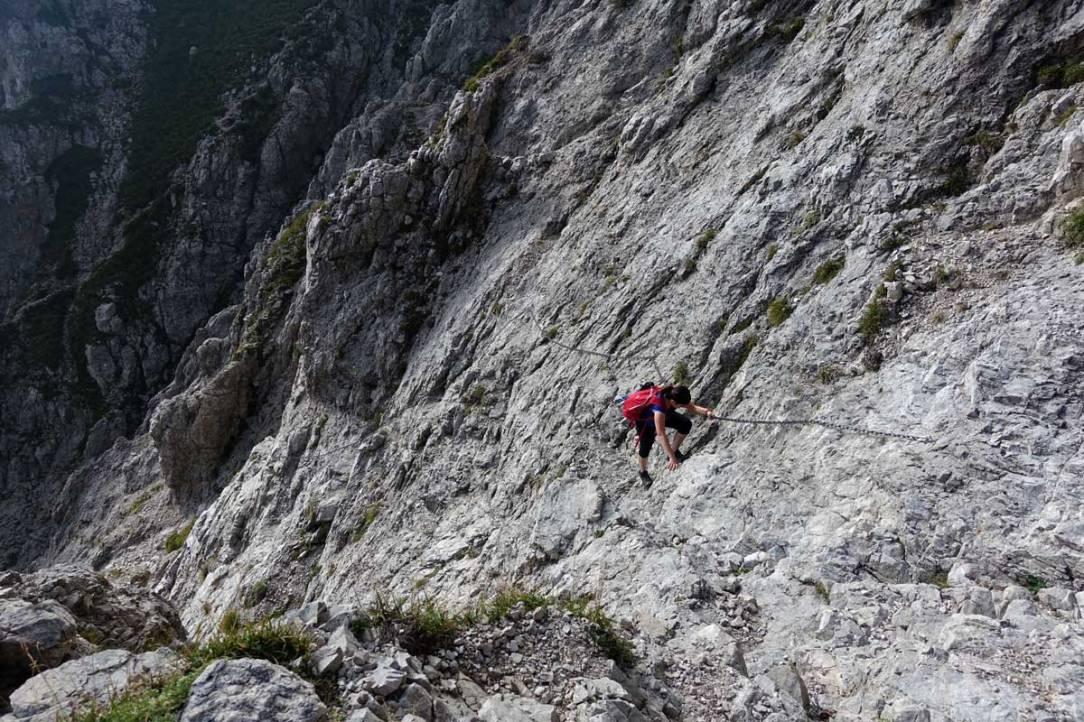 escursionista e un costone di roccia attrezzato con catene