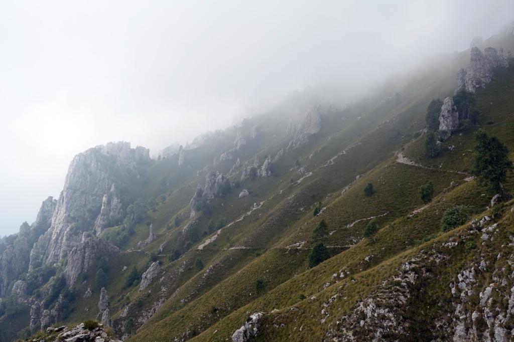 montagne coperte da nuvole e tracce di sentieri