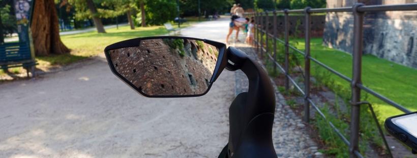 specchietto retrovisore in primo piano alberi e una strada di ghiaia in secondo piano