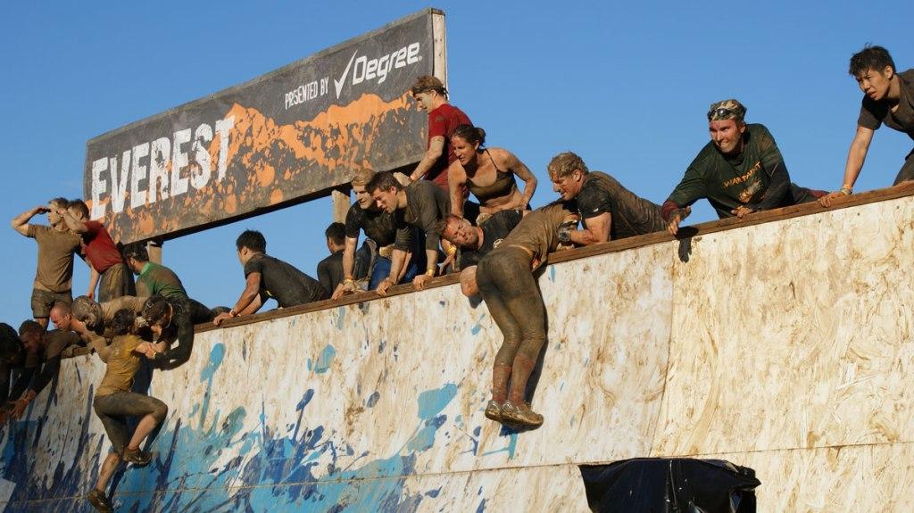 gruppo di atleti ricoperti di fango e una parete da scavalcare
