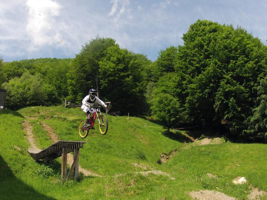 un atleta in mountain bike salta da una passerella