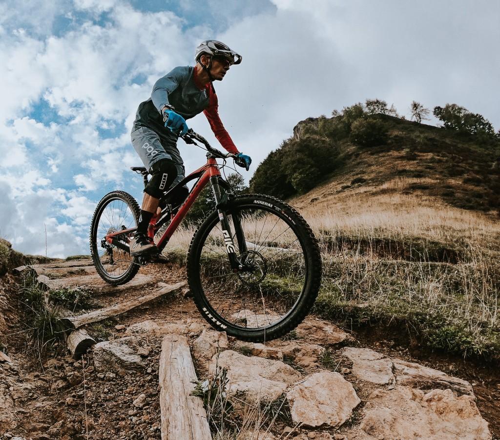 un atleta in mountain bike affronta un passaggio con sassi