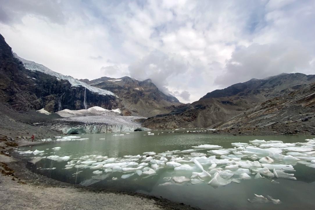 un lago glaciale in primo piano e un ghiacciaio che si scioglie sullo sfondo