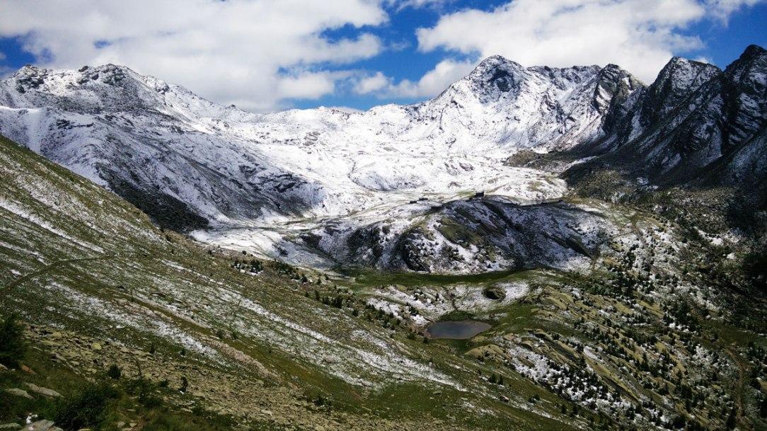 panorama con prati verdi e montagna innevata