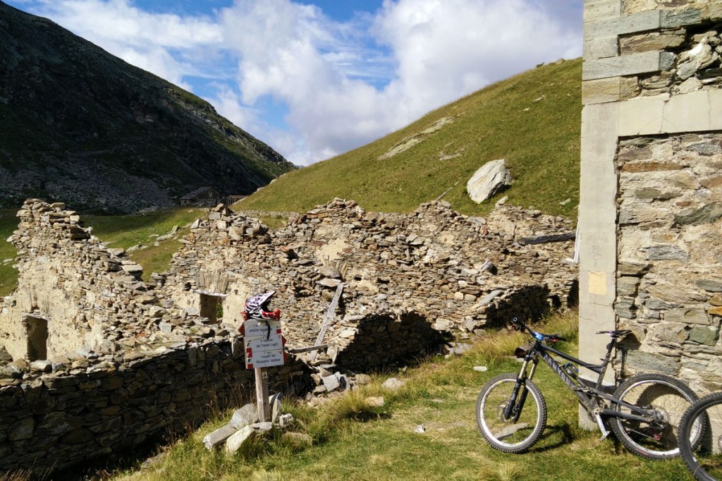 una bicicletta poggiata al muro di una baita di montagna e prati verdi