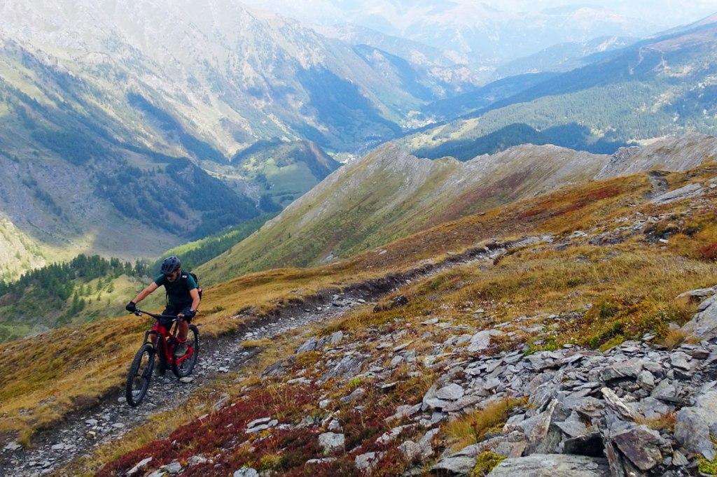 un biker in mountain bike in salita lungo un sentiero che si affaccia su una valle panoramica