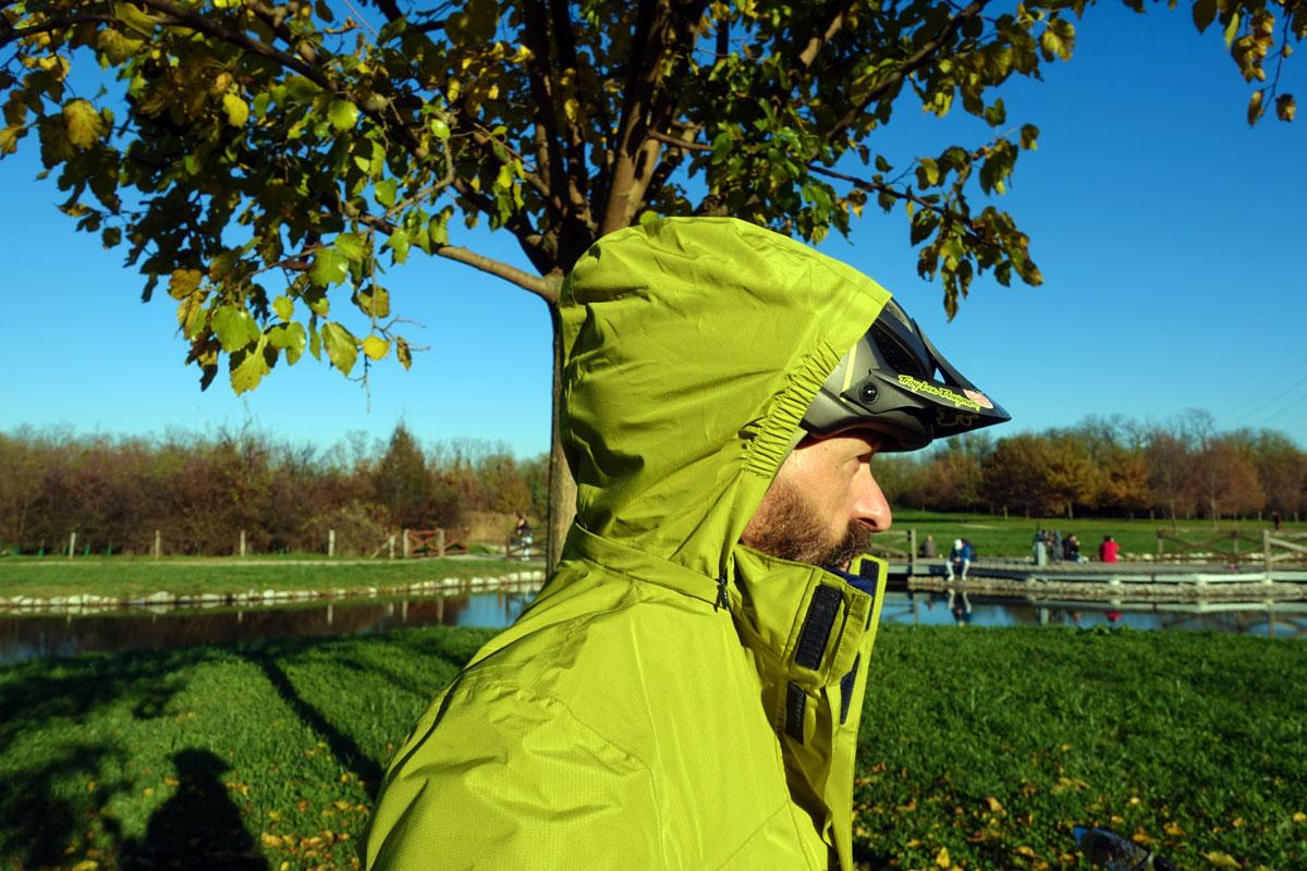 un ciclista indossa il cappuccio della giacca anti pioggia sopra il casco