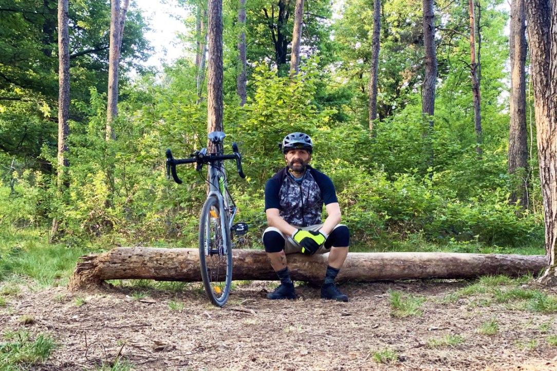 un ciclista seduto su un tronco di albero vicino alla sua bicicletta