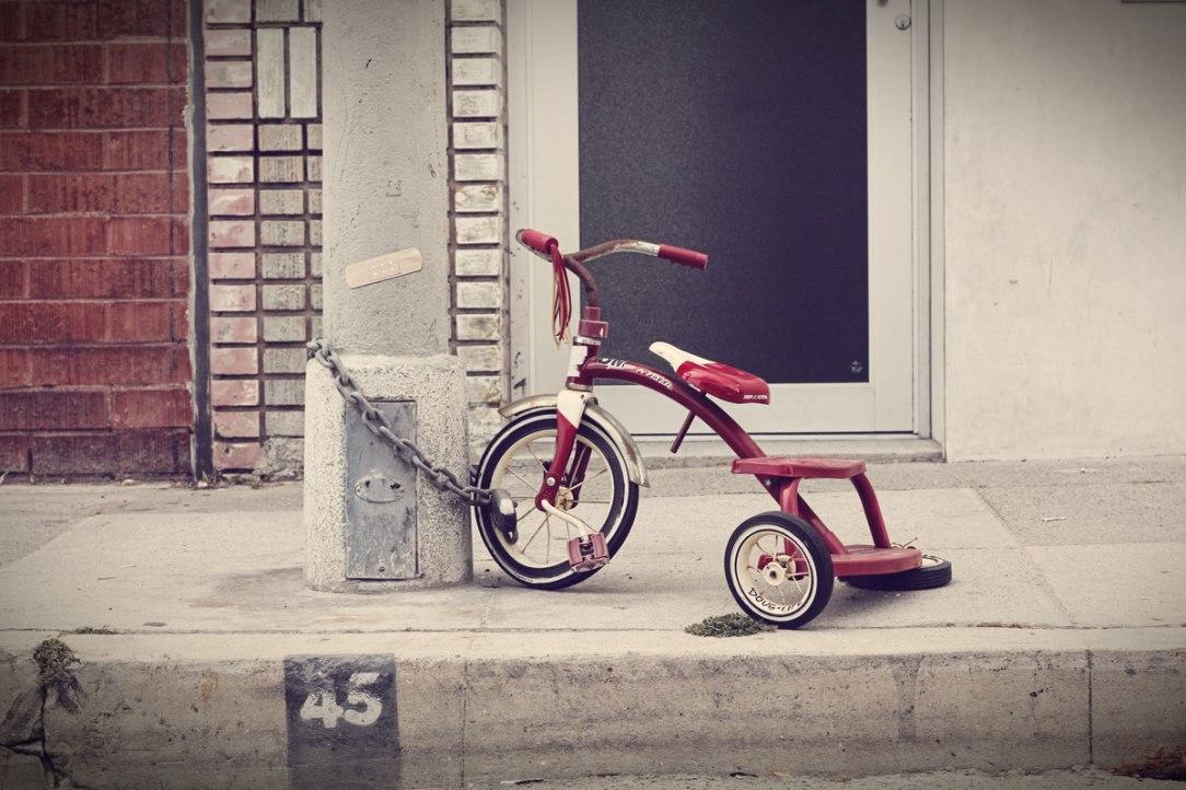 Un triciclo da bambino incatenato ad un palo