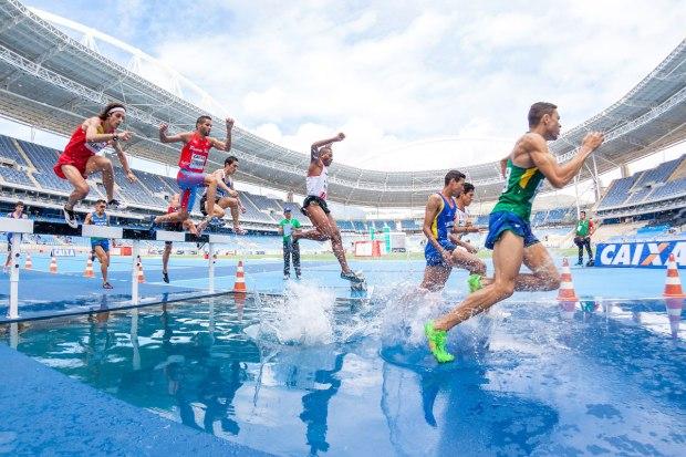 Atleti saltano un ostacolo durante una gara di atletica