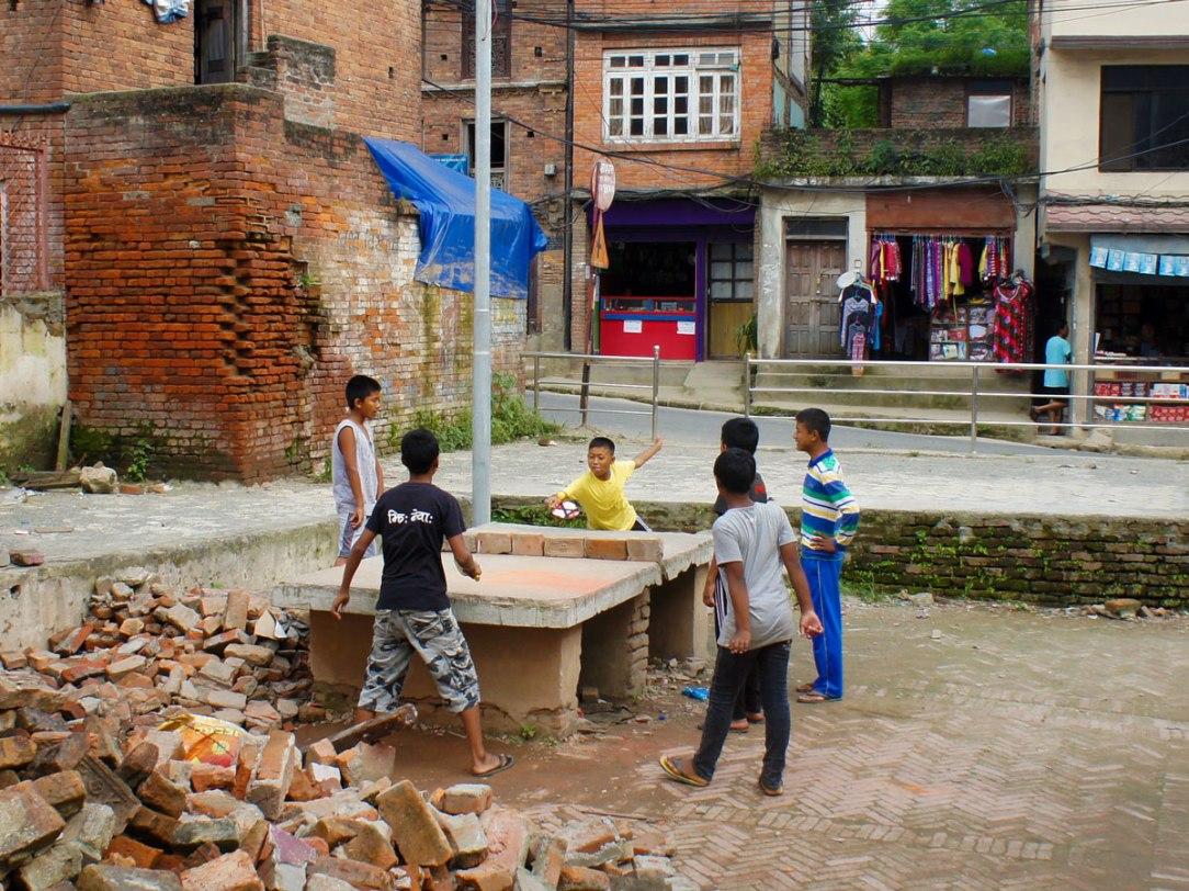 un gruppo di bambini gioca in strada su un tavolo da ping pong improvvisato