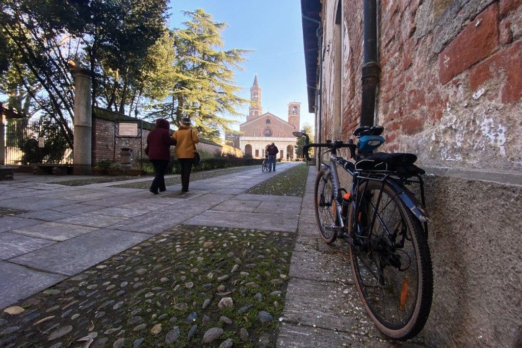 una bicicletta fotografata all'ingresso di un'abbazia e alcune persone a piedi!