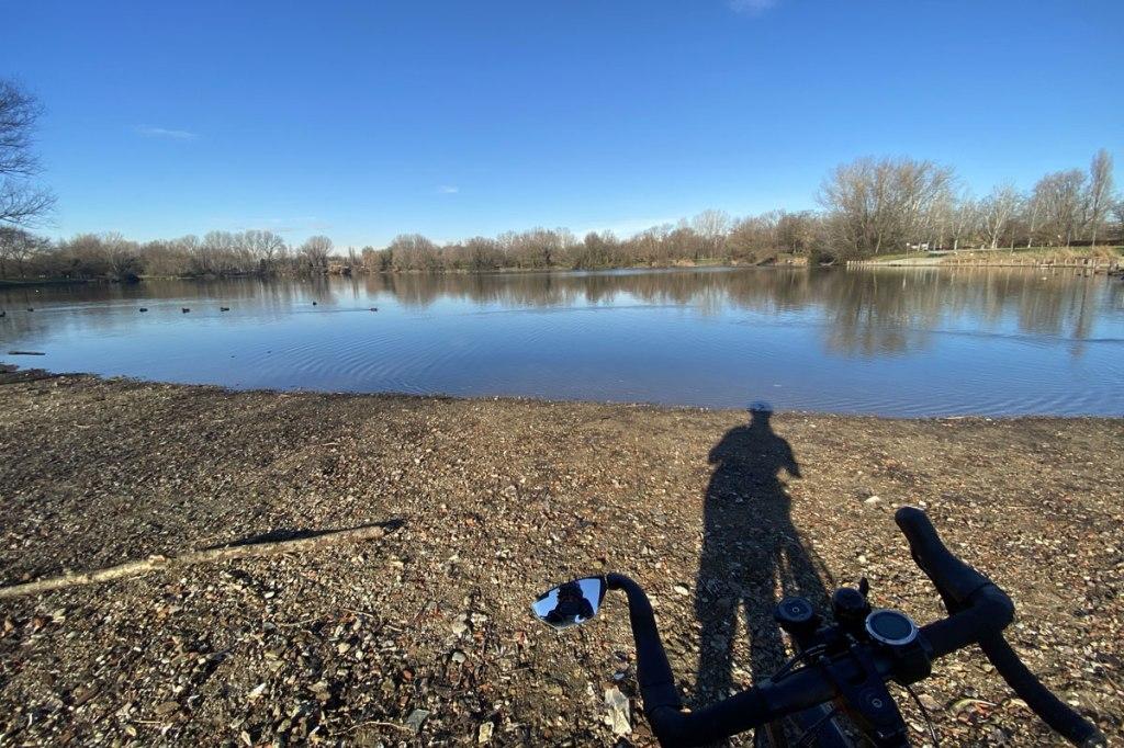 un laghetto all'interno di un parco e in primo paino il manubrio di una bicicletta gravel con specchietto retrovisore