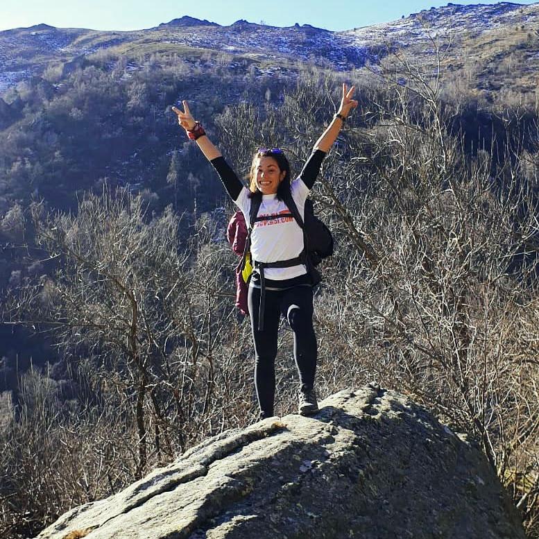 una ragazza felice di aver raggiunto la sua vetta in montagna