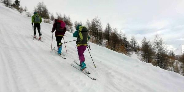 tre ragazzi risalgono un pendio innevato con gli sci da alpinismo
