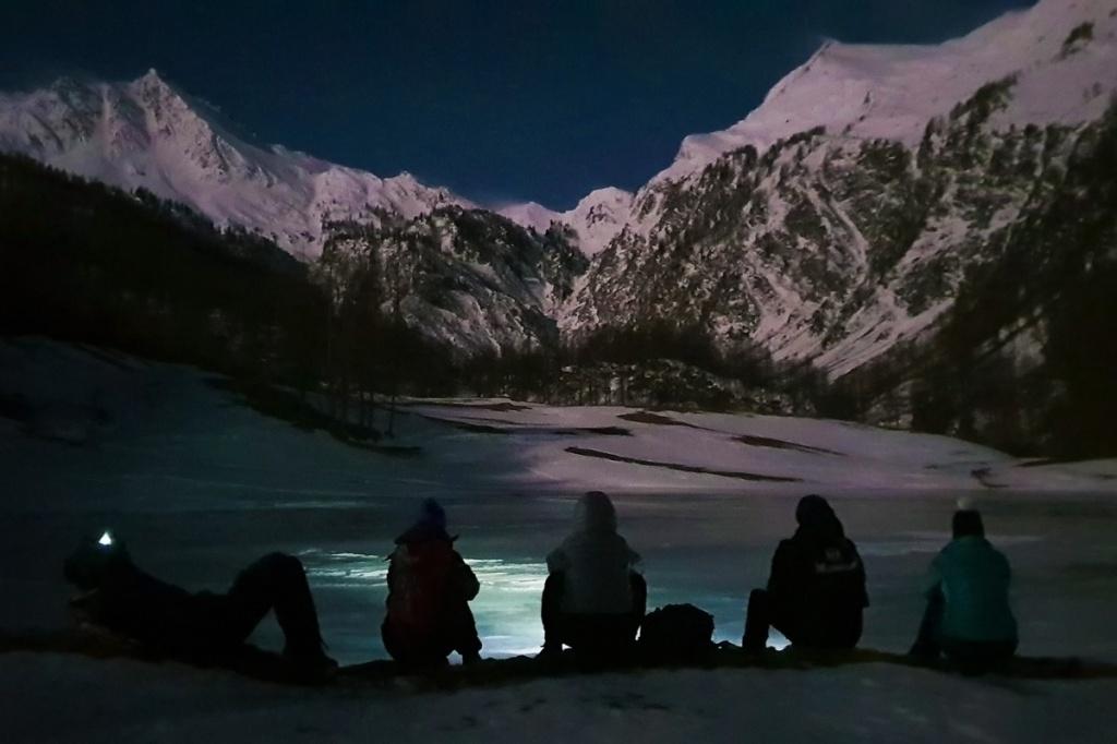 Un gruppo di ragazzi al crepuscolo sulle sponde di un lago ghiacciato nella Conca dei 13 Laghi a Prali