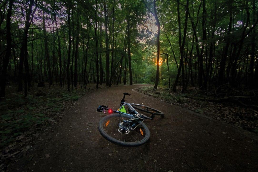 una bicicletta fotografata a terra su una strada sterrata alle luci dell'alba