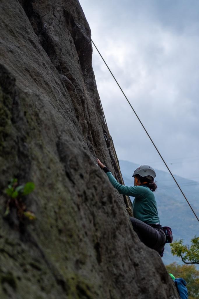 una ragazza arrampica su una parete di roccia