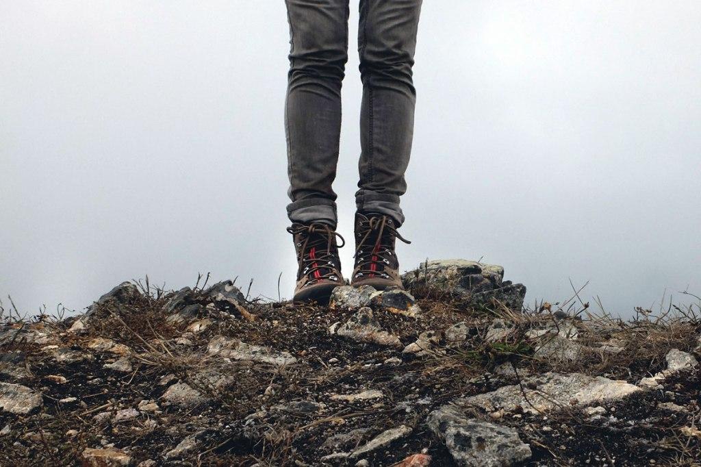 terreno brullo di montagna in primo piano e in secondo piano delle gambe e degli scarponi da montagna con nebbia sullo sfondo